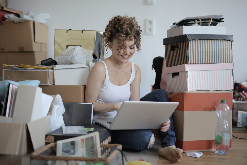 female-shopaholic-with-laptop-shopping-online-in-messy-3791614