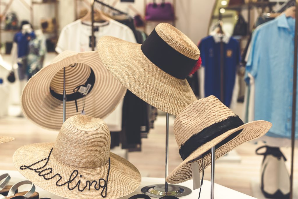 Straw hats ganging in the store. Shopping and travel concept.